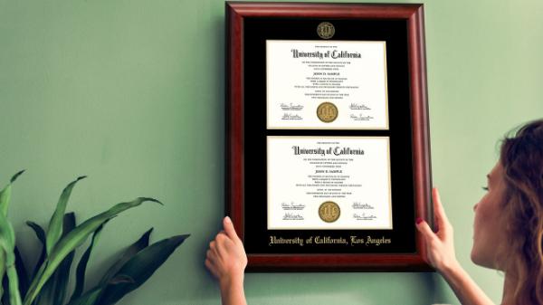 Women hanging diploma frame on wall